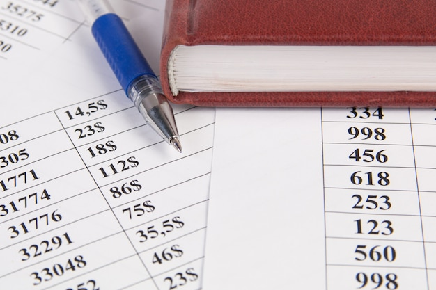 Business concept. financial charts,  notebook and pen