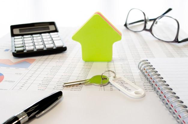 購入、または電卓、眼鏡、ペン、キー、家の形、ドキュメントのある家のために保存するためのビジネスコンセプト。側面図。