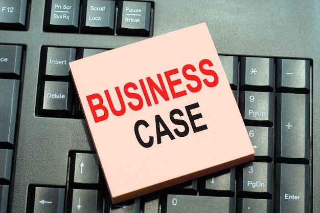 검은 키보드 배경에 스티커 메모 용지에 쓰여진 재무 등급 기록에 대한 비즈니스 개념. 비즈니스 사례를 보여주는 텍스트 캡션 영감을 작성하는 개념적 손.