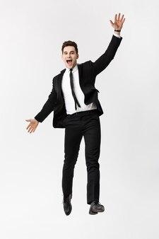 ビジネスコンセプト:フルレングスの肖像画は、腕を上げて成功したハンサムなビジネスマンを興奮させました。灰色の背景に分離。