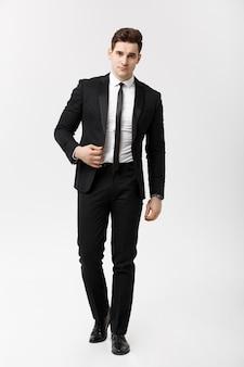 ビジネスコンセプト:白い背景の上を歩くスマートスーツを着たエレガントなビジネスマンの完全な長さの肖像画の写真。