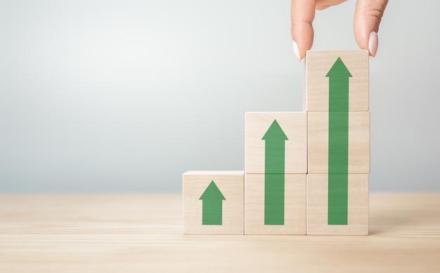 비즈니스 개념 성장 성공 과정, 사업가의 손을 닫고 녹색 화살표가 계단식으로 쌓인 나무 큐브를 배열합니다. 복사 공간, 회색 배경