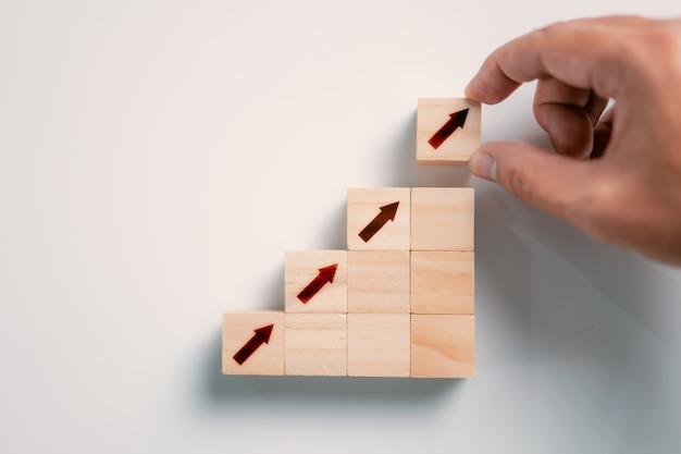 ビジネスコンセプトの成長の成功プロセスステップ階段として木製のブロックの積み重ねを配置する手をクローズアップ