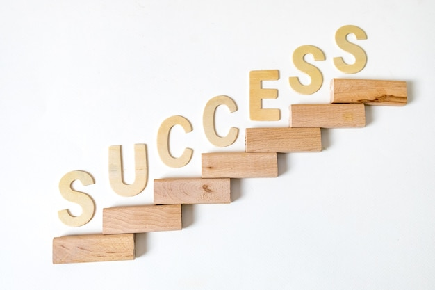 Business concept for growth success process. stairs up as a symbol of career growth up or business success. the word written that success. Premium Photo