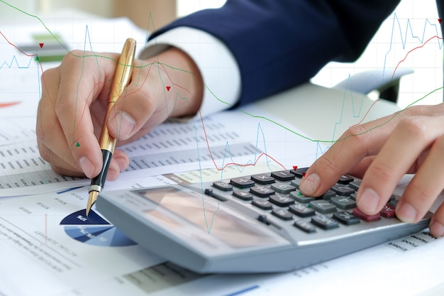Business concept,hand using calculator and hold pen pointing at the graph.