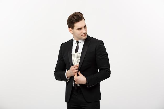 비즈니스 개념: 흰색 배경에 대해 은밀한 표정으로 달러 지폐를 복용하는 검은 양복을 입은 잘생긴 사업가.
