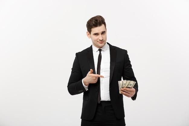 비즈니스 개념: 돈에 손가락을 가리키는 소송에서 잘생긴 사업가. 흰색 배경에 고립.