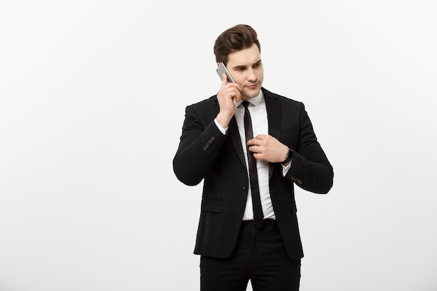 Concetto di affari: bell'uomo d'affari in tuta e parlando al telefono su sfondo grigio isolato.