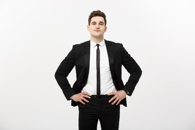 ビジネスコンセプト:ハンサムな男幸せな笑顔若いハンサムな男は、孤立した灰色の背景の上にポーズをとってスマートスーツを着ています。