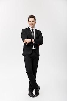 Concetto di affari: bel uomo sorriso felice giovane bel ragazzo in tuta intelligente in posa su sfondo grigio isolato.