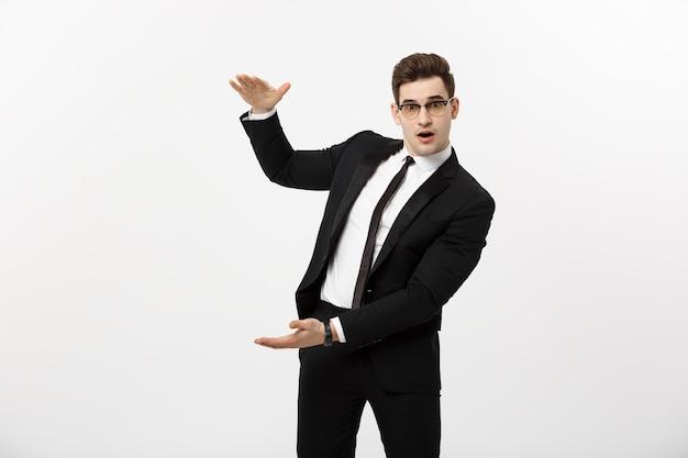 Concetto di affari - bel giovane uomo d'affari sorriso felice, uomo d'affari che mostra qualcosa sul palmo aperto, concetto di prodotto pubblicitario isolato su sfondo bianco
