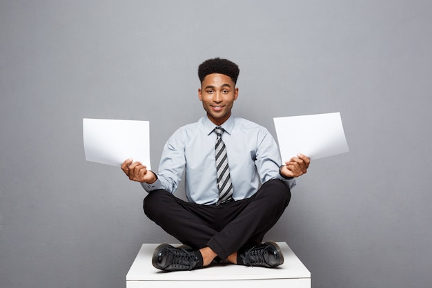 Business concept - handsome young professional african american businessman holding report papers.