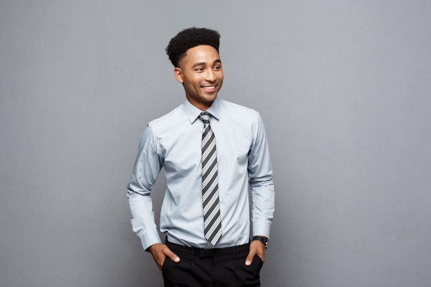 Business concept - happy confident professional african american businessman posing over grey wall.