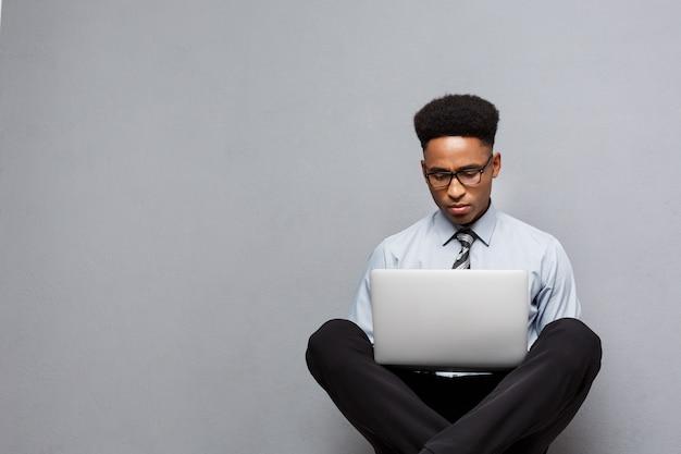 ビジネスコンセプト-幸せなハンサムなプロのアフリカ系アメリカ人ビジネスマンは、ラップトップで遊ぶのを楽しんでいます。