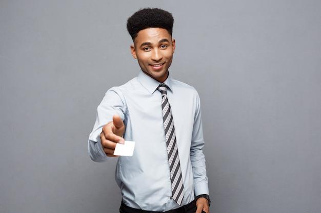 Бизнес-концепция - счастливый красивый профессиональный афро-американский бизнесмен, давая имя карты клиенту.