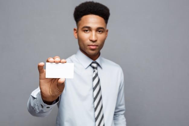 Бизнес-концепция - счастливый красивый профессиональный афро-американский бизнесмен, показывая имя карты для клиента.