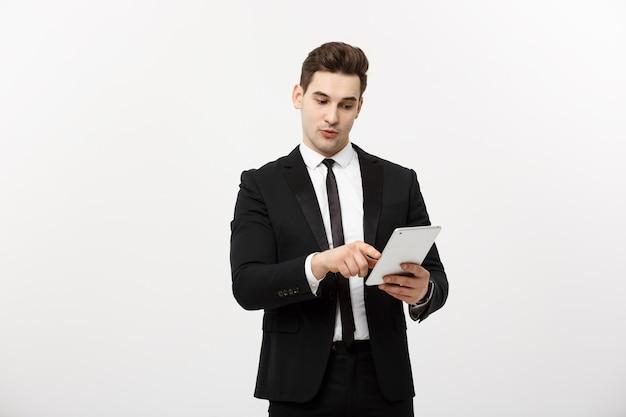 Concetto di affari: uomo d'affari sorridente felice che indica sulla compressa digitale su fondo bianco