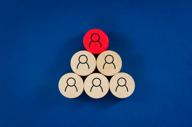 Business concept image of wooden pegs with people icons over blue space, human resources and management concept.