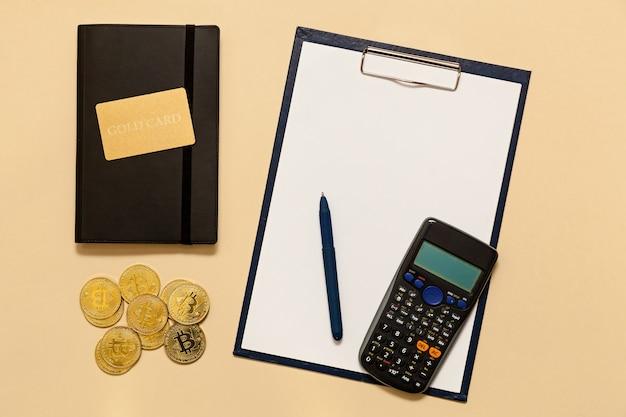 テーブルの上のビジネスコンセプトアイテムゴールドビットコイン、ドル、日記、ゴールドカード、ベージュの背景の電卓。ビットコインはデジタル通貨であり、貿易と両替の世界市場です。