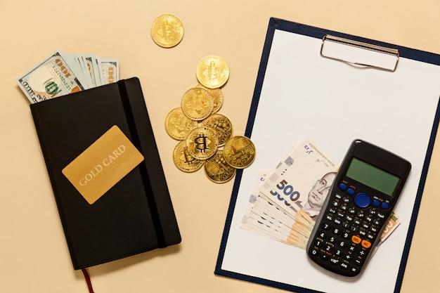 Предметы бизнес-концепции на столе золотые биткойны, доллары, дневник, золотая карта, калькулятор на бежевом фоне. биткойны - это цифровая валюта, мировой рынок торговли и обмена денег.
