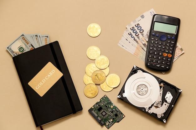 テーブルの上のビジネスコンセプトアイテムゴールドビットコインドル日記ゴールドカードハードディスク