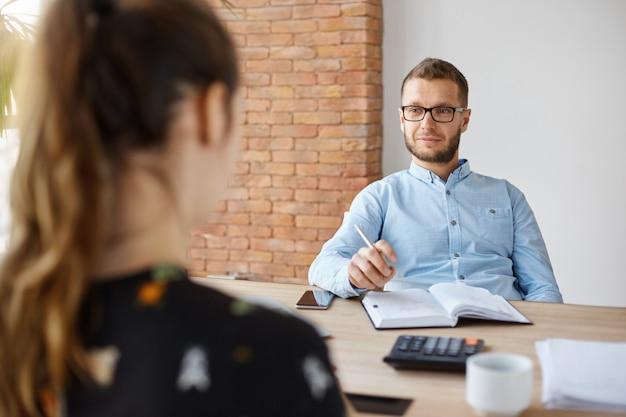 Бизнес-концепция собеседование. взрослый бородатый мужчина менеджер по персоналу в очках и рубашке сидит в светлом офисе перед брюнеткой кавказской женщиной, задавая вопросы о предыдущем рабочем месте