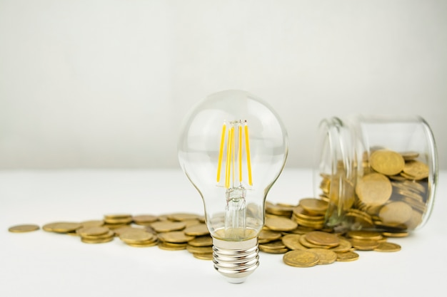 Business concept. lamp with coins on a light table. business ideas, brainstorming. recovery and business growth. copy space