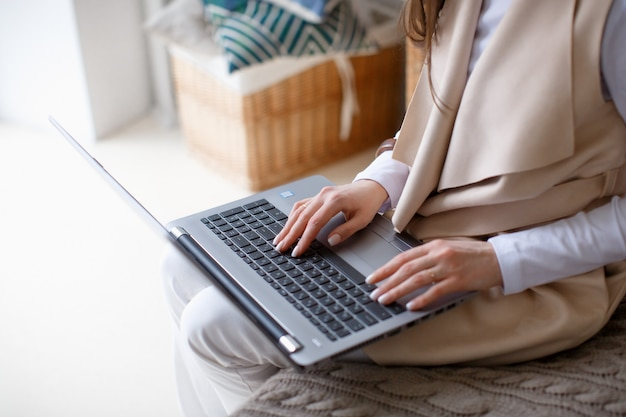 Business concept, laptop and woman's hands on the keyboard,  side view, close up