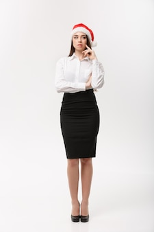 Business concept  modern caucasian business woman in christmas theme thinking pose on white  wall with copy space