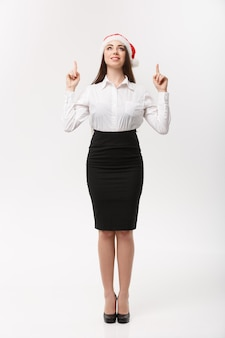 Business concept  modern caucasian business woman in the white  wall pointing finger upward presenting product