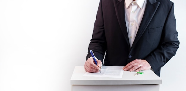 Business concept mortgage loan. man in black suit filling out document on white