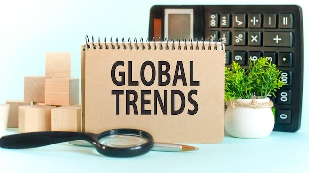 Бизнес-концепция. блокнот с текстом global trends лист белой бумаги для заметок, калькулятор, блоки woden, увеличительное стекло, на стене диаграмм