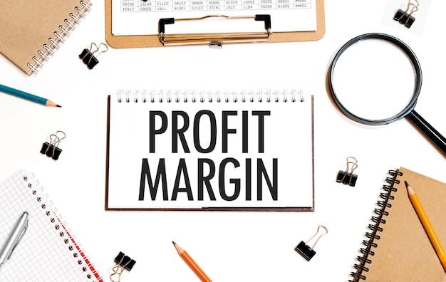 Бизнес-концепция. блокнот с текстом profit margin лист белой бумаги для заметок, калькулятор, очки, карандаш, ручка, на белом фоне