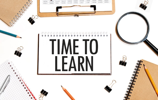 Бизнес-концепция. блокнот с текстом «время учиться». плоская планировка