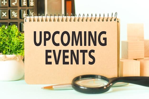 Бизнес-концепция. блокнот с текстом предстоящие события лист белой бумаги для заметок, калькулятор, блоки, лупа