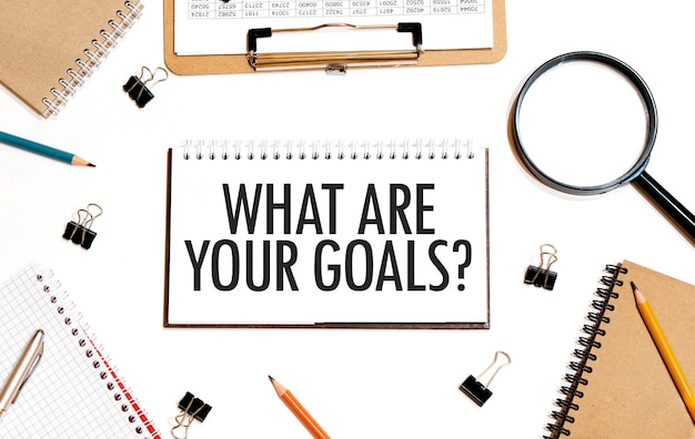 Business concept. notebook with text what are your goals sheet of white paper for notes, calculator, glasses, pencil, pen