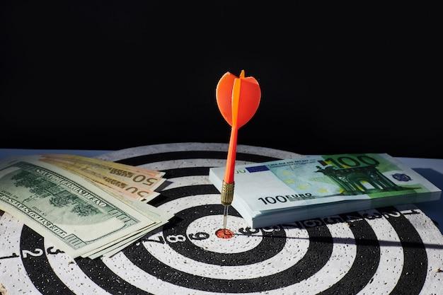 お金と目標の達成のビジネスコンセプト。ダーツ、現金紙幣のドルとユーロ。