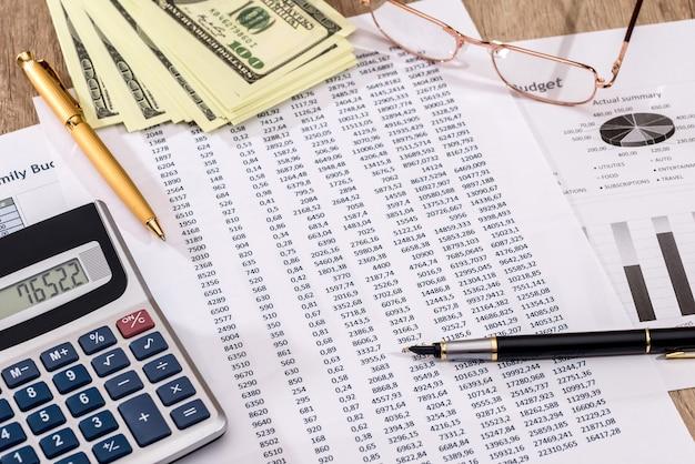 オフィスワーキングのビジネスコンセプト-コスト年間予算を数えます。
