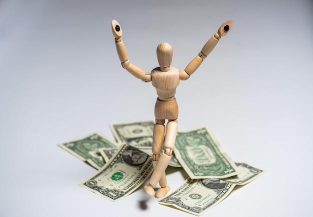 Фото бизнес-концепции. деревянный человек с деньгами. заработок и зарплата