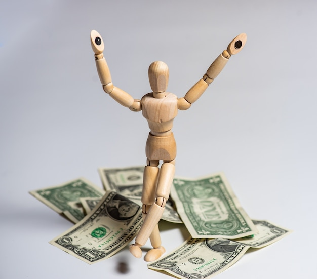 Business concept photo. wooden man with money. earnings and salary