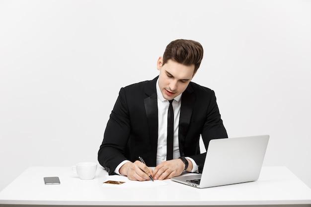 Concetto di affari: ritratto concentrato giovane uomo d'affari di successo che scrive documenti alla scrivania luminosa dell'ufficio.