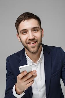 Concetto di business - ritratto bello uomo d'affari che gioca telefono con sorridente volto sicuro. sfondo bianco.