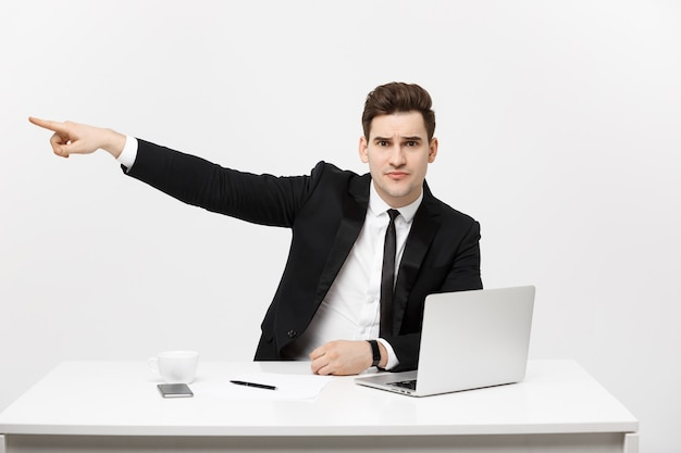 Business concept portrait of handsome businessman dressed in suit sitting in office pointing finger ...