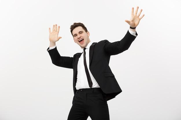 비즈니스 개념: 흰색 배경 위에 격리된 손을 들고 놀라움과 기쁨을 표현하는 세로 잘생긴 사업가입니다.