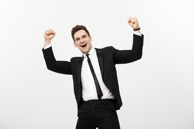 Il concetto di business: ritratto bello uomo d'affari che esprime sorpresa e gioia alzando le mani, isolato su sfondo bianco.