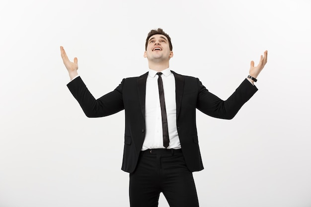 Business concept: portrait handsome businessman expressing surprise and joy raising his hands, isolated over white background.