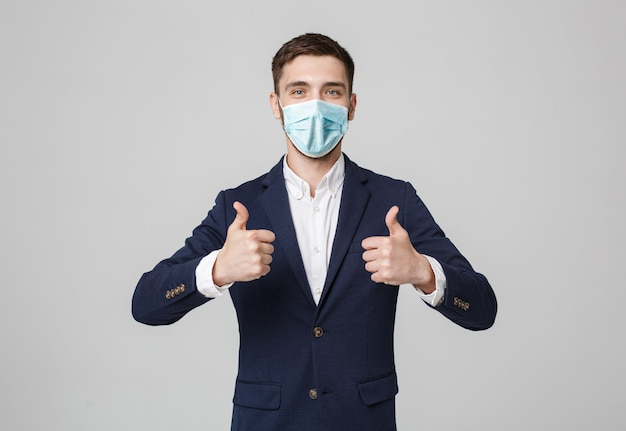 Business concept - portrait handsome businessman in face mask giving double thump up. isolated on white wall.