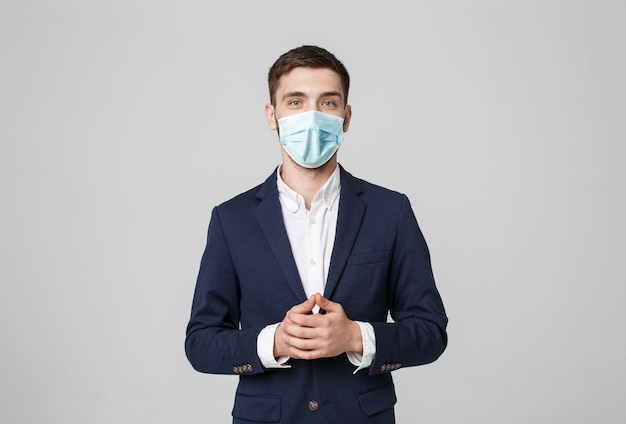 Business concept - portrait handsome businessman in face mask holding hands with confident face. white wall.