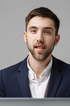 ビジネスコンセプト - 肖像画ハンサム幸せハンサムビジネスマン笑顔と作業場でsiting訴訟で。白色の背景。