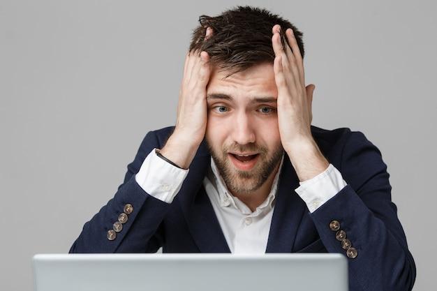 ビジネスコンセプト - 肖像画ハンサムでストレスフルビジネスの男は、ノートパソコンで仕事を見てショックショックで。白色の背景。